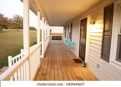 Long front porch covered with a teal table/chair set. Porch swing at the end of the porch.