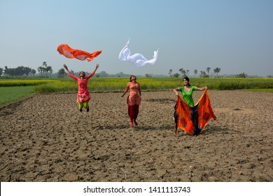 Long front shot of three girls wearing colorful salwar kameez in a paddy harvested field in rural area enjoying, jumping in air flying their urna/cloth in air, background blue sky and yellow mustard,