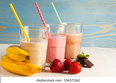 Long glasses of milkshakes with chocolate, strawberry, banana, with ice cream on white and blue background. Shakes and smoothies. Milk shake and cocktail for summer.