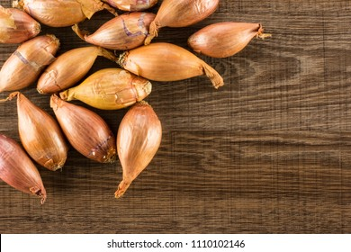 Long golden shallots flatlay isolated on brown wood background