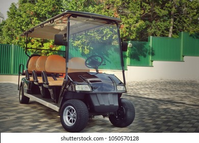 Long Golf Electric Cart At The Beach Lift Station On The Paving Road To The Hotel. Black Empty Shuttle Eight Seat Electro Car On The Area Near Elevator To Sea Beach.