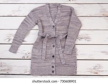 Long gray cardigan on white wooden background. Simple design of knitwear. Woolen yarn blended with shimmer. New casual women's apparel.