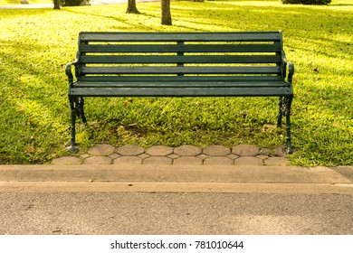 long green bench in park at the morning