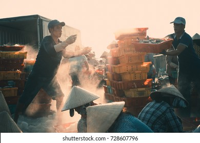 Long Hai, Ba Ria, Viet Nam - July 15 2017: Local people working at marketplace, woman is selective fish and man is carry basket fresh fish from ship on the beach. Vintage colour with backlight of sun