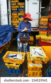 LONG HAI, VIET NAM- JULY 15. Fish placed in plastic trays, transported to wholesale at fishing market, man arrange fish plastic tray, women stand surround and look at those in Vietnam July 15, 2013