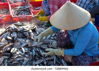 Long Hai,Ba Ria-Vung Tau, Viet Nam. Local people working at marketplace, woman is selective fish and man is carry basket fresh fish from ship on the beach. Vintage colour with backlight of sun