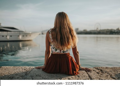 Long hair blonde woman sitting on the sea port edge, looking to the sea at sunset.