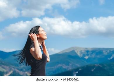 Long hair brunette girl on the top of the mountain enjoying fresh air