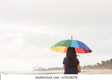 Long hair brunette girl with rainbow umbrella on cloudy day