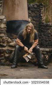 long hair Brutal man with axes near forest house
