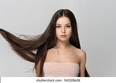 Long hair fluttering in the wind. Beautiful woman with bare shoulders has a clean well-groomed skin and long straight hair. Close-up portrait against a light gray background.