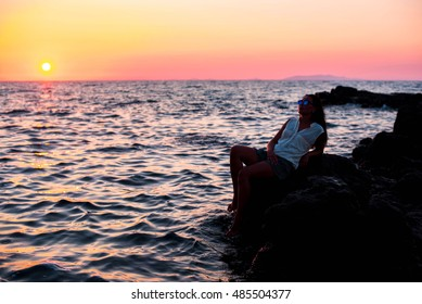 Long hair girl sitting on the stone at sunset time