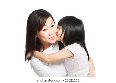 Long hair little chinese girl giving her mother a kiss on the cheeks.