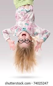 Long hair little girl hanging by her feet