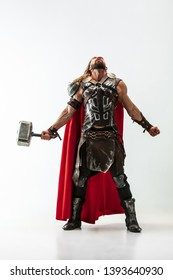 Long hair and muscular male model in leather viking's costume with the big hammer cosplaying isolated on white studio background. Half-lenght portrait. Fantasy warrior, antique battle concept.