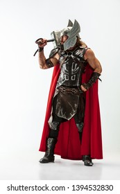 Long hair and muscular male model in leather viking's costume with the big hammer cosplaying isolated on white studio background. Full-lenght portrait. Fantasy warrior, antique battle concept.