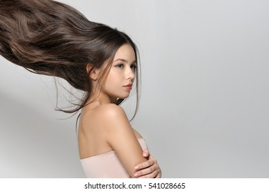 Long hair thrown up. Beautiful woman with bare shoulders has a clean well-groomed skin and long straight hair. Close-up portrait against a light gray background.