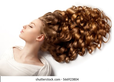 Long hair. Waves Curls updo hairstyle in salon. Fashion model, woman with healthy shiny hair. Girl with luxurious volume haircut.