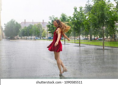 Long hair woman in red dress crazy dancing in the rain at the middle of city square, turning around, she is smiling and enjoying warm weather summer rainy drops