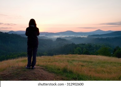Long hair woman stand on meadow with golden stalks of grass and watch over misty and foggy morning valley to sunrise