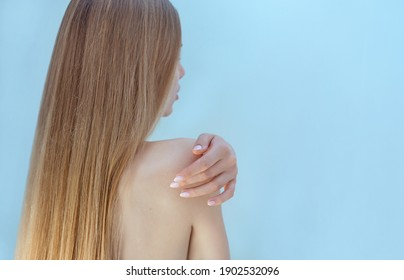 Long hair woman touching her shoulder by hand. Cosmetics, natural, moisturizing, tenderness concept