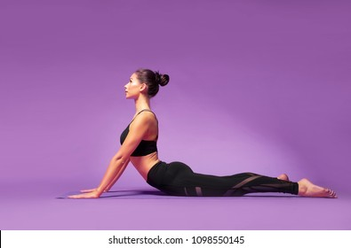 Long haired beautiful pilates or yoga athlete does a graceful pose while wearing a tight sports outfit against a bright purple background in a studio