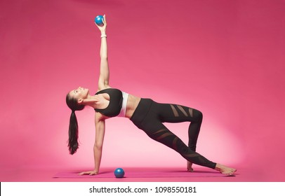 Long haired beautiful pilates or yoga athlete does a graceful pose with blue exercise balls while wearing a tight sports outfit against a pink background in a studio