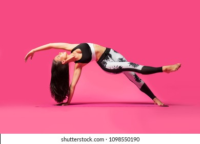 Long haired beautiful pilates or yoga athlete does a graceful pose while wearing a tight sports outfit against a pink background in a studio