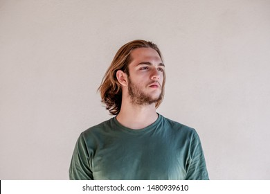 Long haired blonde man looking right, handsome bearded young guy turn the right, isolated photo