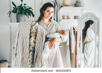 Long haired brunette chooses clothes in the wardrobe and holding little baby in arms and looks at striped jacket to suit at home.