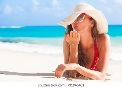 long haired girl in bikini and straw hat blowing a kiss on tropical caribbean beach