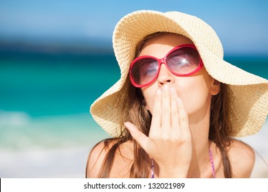 long haired girl in straw hat blowing a kiss on tropical boracay beach