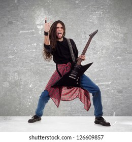 long haired guitarist is playing and making a rock hand gesture