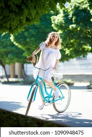Long haired happy young beautiful woman in a dress riding her bicycle in the city smiling to the camer enjoying summertime outdoors adventure trip vacation travel tourism vehicle transport.