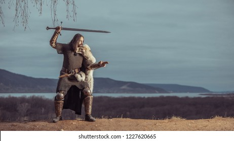 Long haired knight with the two-handed sword. Medieval rural background.