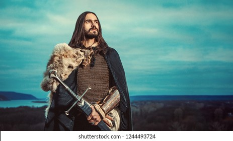 Long haired knight with the two-handed sword. Panorami? view on the background.