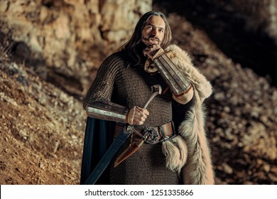 Long haired knight with the two-handed sword. Rocks on the background.