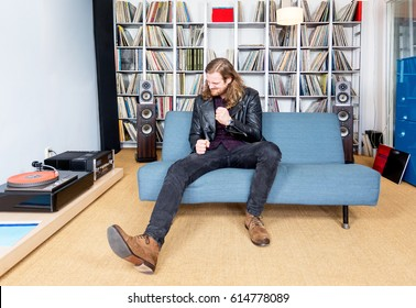 long haired man intensely ejoying rock music from vinyl  long playing record, on his sofa