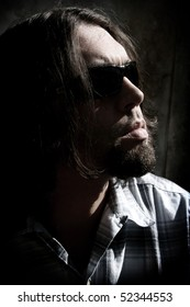 Long haired man with sunglasses in a low key shot