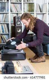 long haired man turning over an long playing record on a high-end turntable