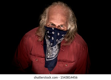 A long haired masked bandit wearing a blue bandana to cover the face and a red shirt glaring at viewer with dark background.