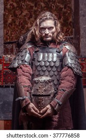 Long haired medieval knight in the armor with the helmet.
