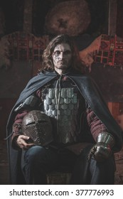 Long haired medieval knight in the armor with the helmet. Low contrast post-processing.