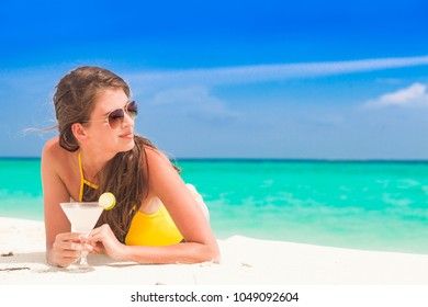 long haired woman in bikini relaxing at white sand beach with margherita cocktail