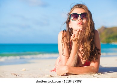 long haired woman in bikini and straw hat blowing a kiss on tropical beach