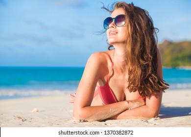 long haired woman in bikini and sunglasses lying on tropical beach