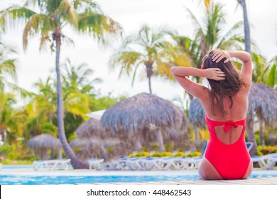 long haired woman in red one piece swimsuit relaxing by the pool, remote tropical beaches and countries. travel concept