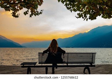 A long haired woman is sitting on a bench and wathcing the sunset as it goes down over the lake and the mountains in Ascona, Switzerland.