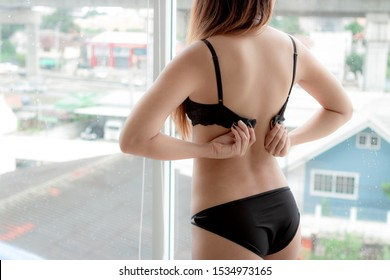 Long haired woman wearing black bra standing in the window is removing the button from undergarment.In the daytime it was raining. Cool weather the woman stood looking out of the glass in her bedroom.