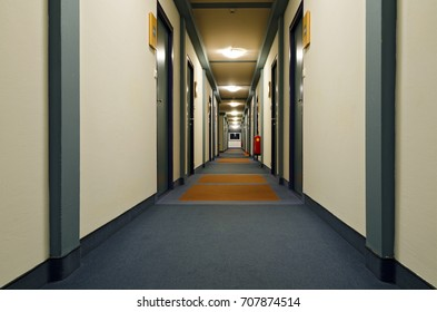 Long hallway of a hotel with room doors on each side at night